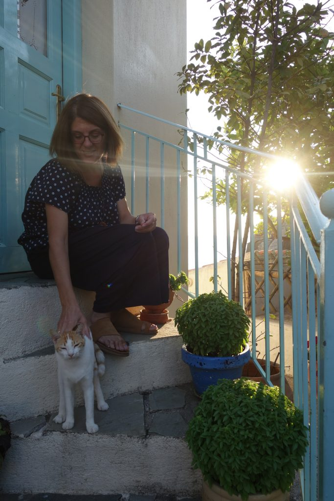 Kyriaki petting cat by entrance of Eleanora's Cottage